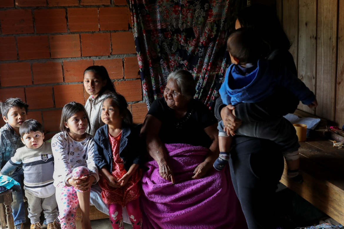 """Vanda Kamlem, 87, sits surrounded by her grandchildren at her house in Xokleng Laklano Indigenous land. """"We cannot plant food living in this hole. They want to get rid of us. They don't like us,"""" said Vanda. A former midwife, Vanda remembers the days when she gathered pine nuts from the abundant Araucaria pines, known as monkey-puzzle trees. Now, the forests have been cut down and fish have become scarce as the rivers turned cloudy, she said. [Amanda Perobelli/Reuters]"""