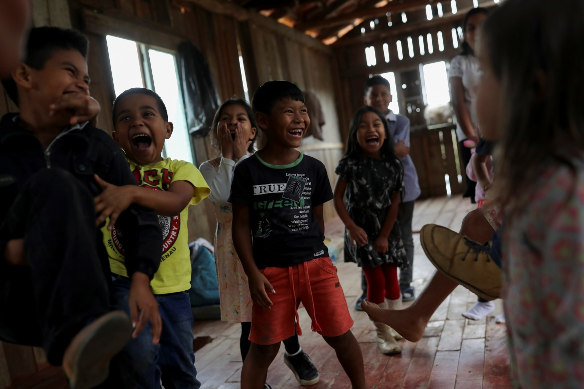 Children play as their parents participate in a prayer in Xokleng Laklano Indigenous land. Across Brazil, the Supreme Court ruling will affect hundreds of Indigenous land claims, many of which offer a bulwark against deforestation in the Amazon rainforest. [Amanda Perobelli/Reuters]