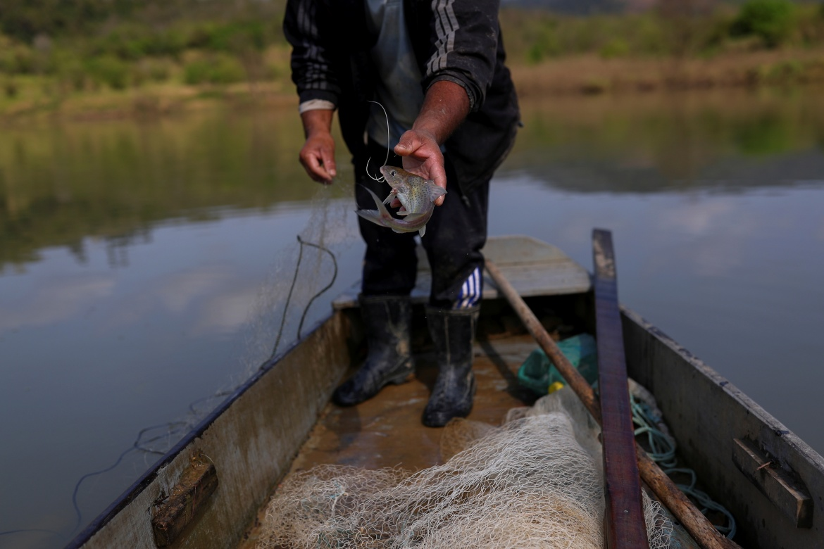 Fisherman Luiz Cabral, 52, throws a fish in a wooden canoe on the Itajai river near the north dam, on Xokleng Laklano Indigenous land. [Amanda Perobelli/Reuters]