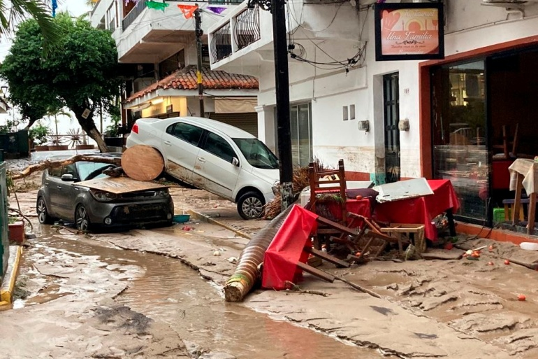 Damaged cars are pictured on a flooded street after Hurricane Nora pounds Mexico's coast with heavy rains and strong winds in Puerto Vallarta, in Jalisco state, Mexico August 29, 2021 [Alfonso Lepe/ Reuters]