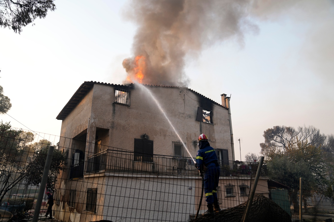 The forest blaze on the outskirts of Athens raced into residential areas on Tuesday, forcing thousands to flee. [Michael Varaklas/AP Photo]