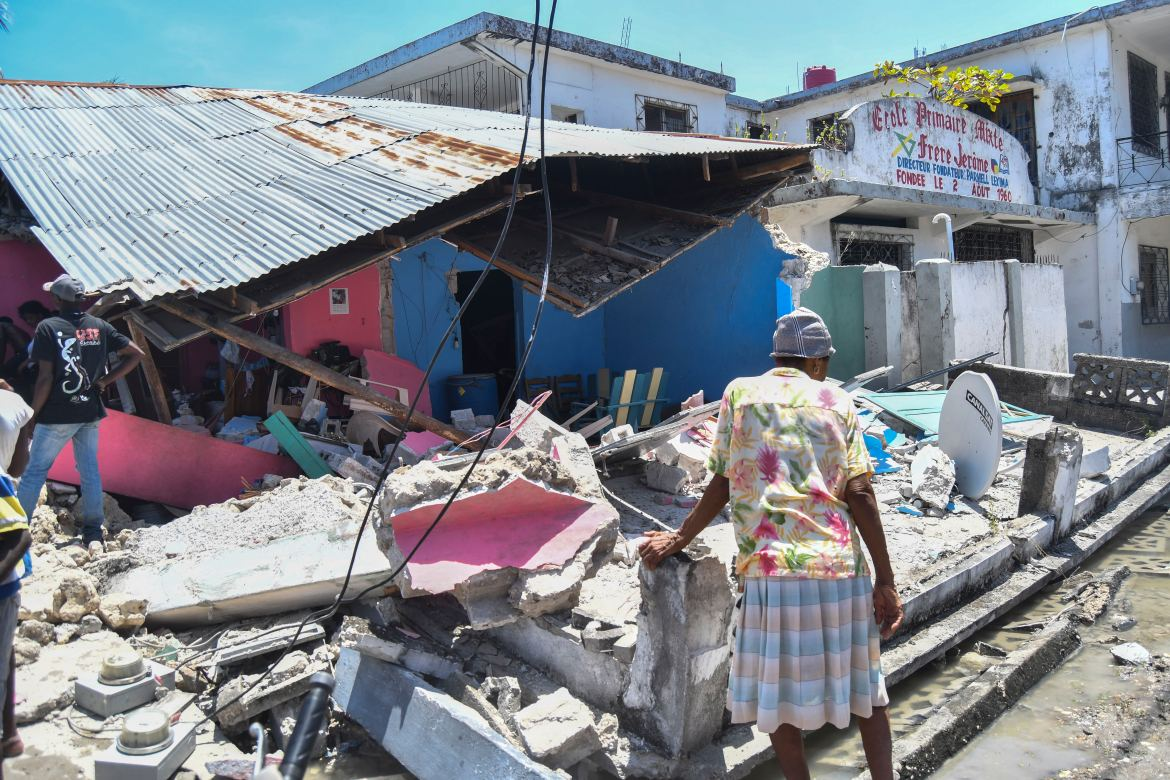 A woman stands in front of a destroyed home in the aftermath of an earthquake in Les Cayes, Haiti. [Duples Plymouth/AP Photo]