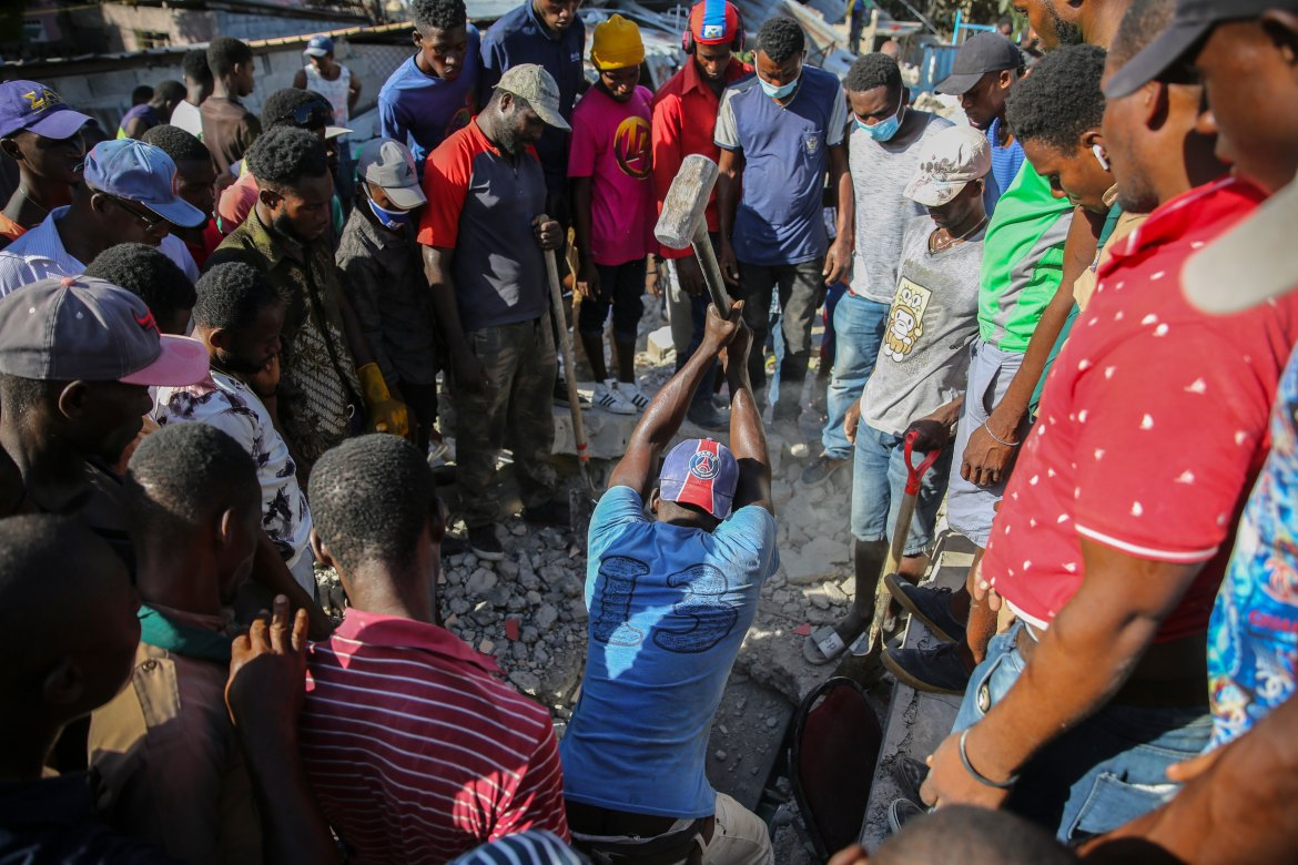 A man uses a sledgehammer to break through the rubble of a home destroyed by the earthquake in Les Cayes. [Joseph Odelyn/AP Photo]