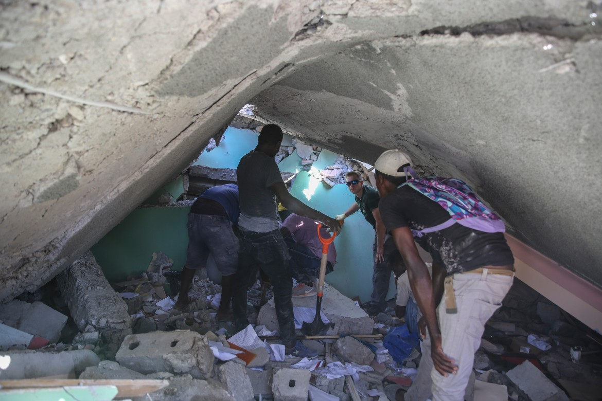 People search for survivors in a home destroyed by the major temblor. [Joseph Odelyn/AP Photo]