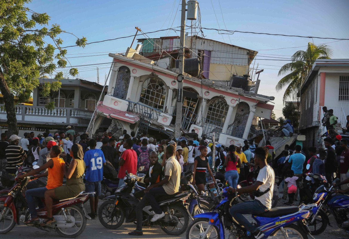 People gather outside the Petit Pas Hotel, which was destroyed by the earthquake in Les Cayes. [Joseph Odelyn/AP Photo]
