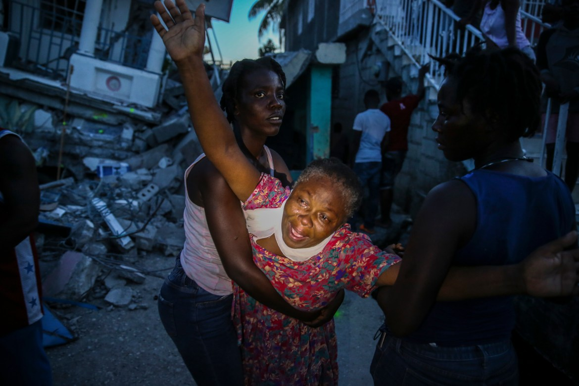 Oxiliene Morency cries out in grief after the body of her seven-year-old-daughter Esther Daniel was recovered from the rubble of their home. [Joseph Odelyn/AP Photo]