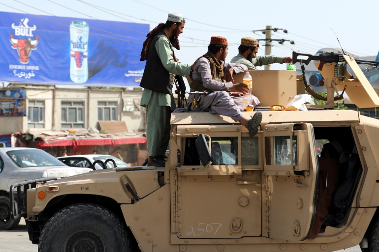 Taliban fighters stand guard in front of Hamid Karzai International Airport, in Kabul, Afghanistan, after the group seized control of the capital [Rahmat Gul/AP Photo]