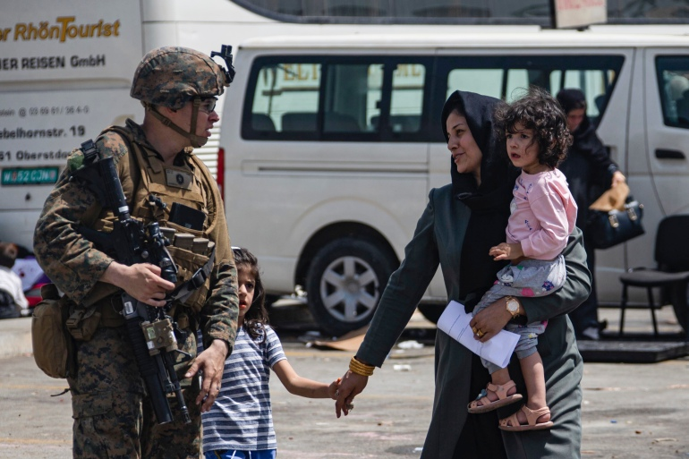 A US Marine escorts evacuees at Hamid Karzai International Airport, in Kabul, Afghanistan, Friday, Aug. 20, 2021 [Cpl. Davis Harris/US Marine Corps via AP Photo]