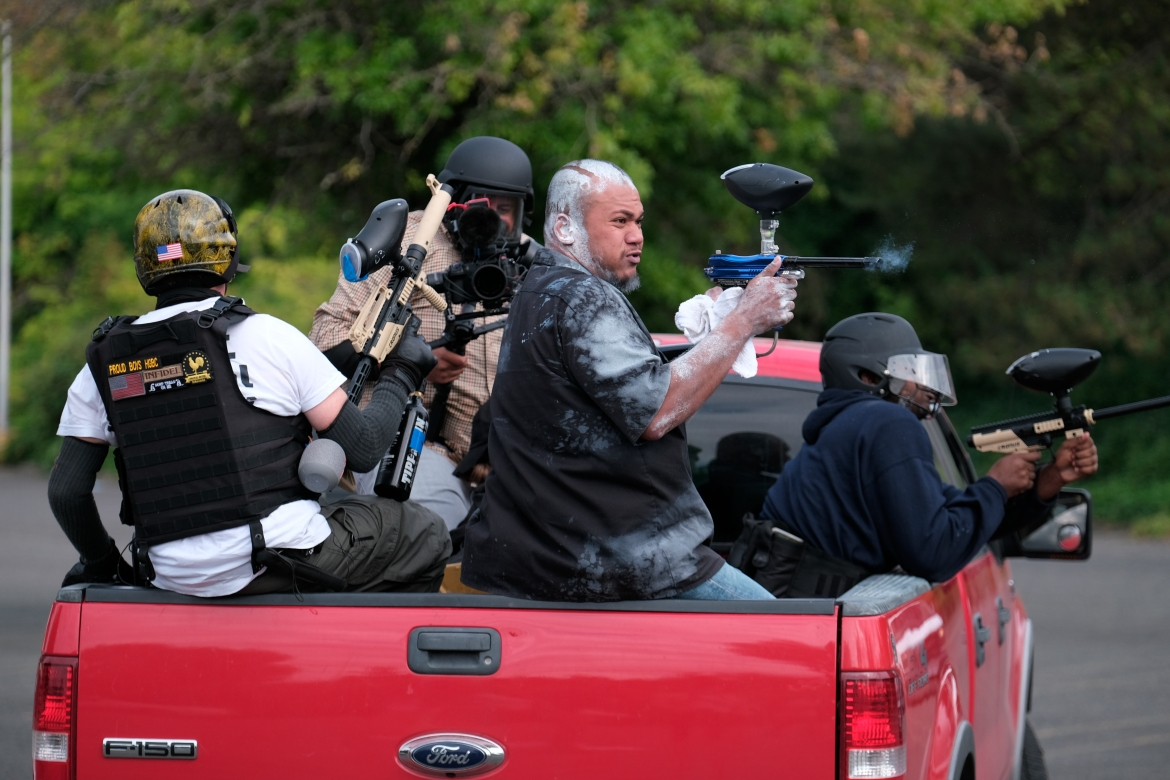 Tusitala 'Tiny' Toese, a member of the far-right group Proud Boys, fires paintball rounds at anti-fascist protesters as they depart from their rally. [Alex Milan Tracy/AP Photo]