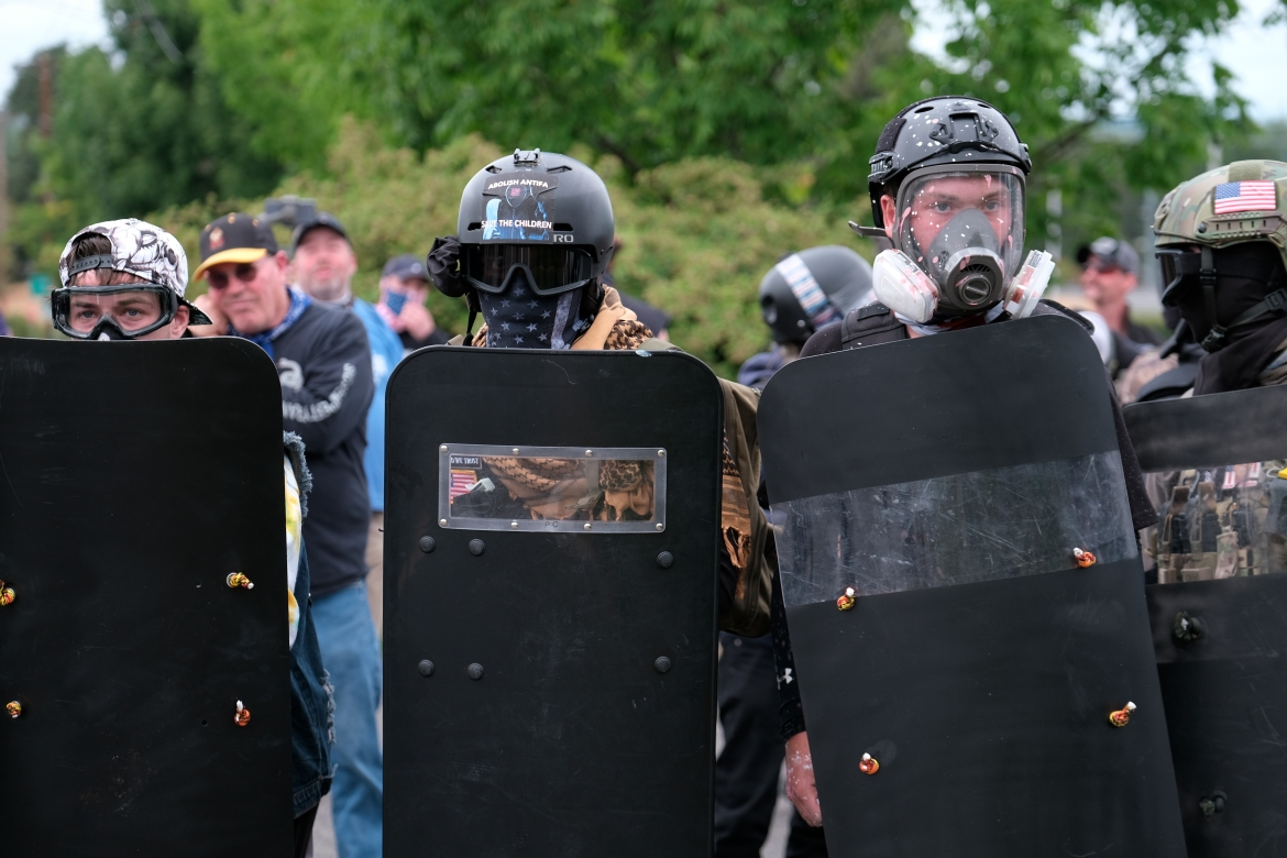 Members of the far-right group Proud Boys take a defensive formation and hold shields as they face off with anti-fascist counterprotesters. [Alex Milan Tracy/AP Photo]