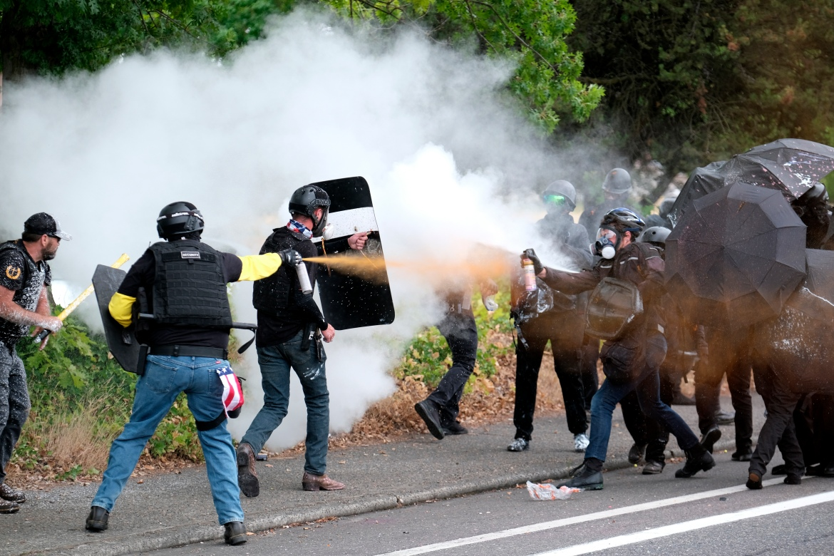 Members of the far-right group Proud Boys and anti-fascist protesters spray bear mace at each other during clashes between the politically opposed groups in Portland. [Alex Milan Tracy/AP Photo]
