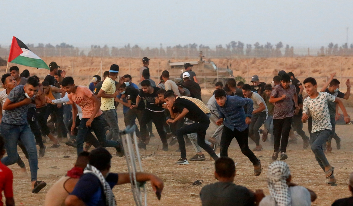 Protesters run and take cover from teargas fired by Israeli soldiers. [Abdel Kareem Hana/AP Photo]