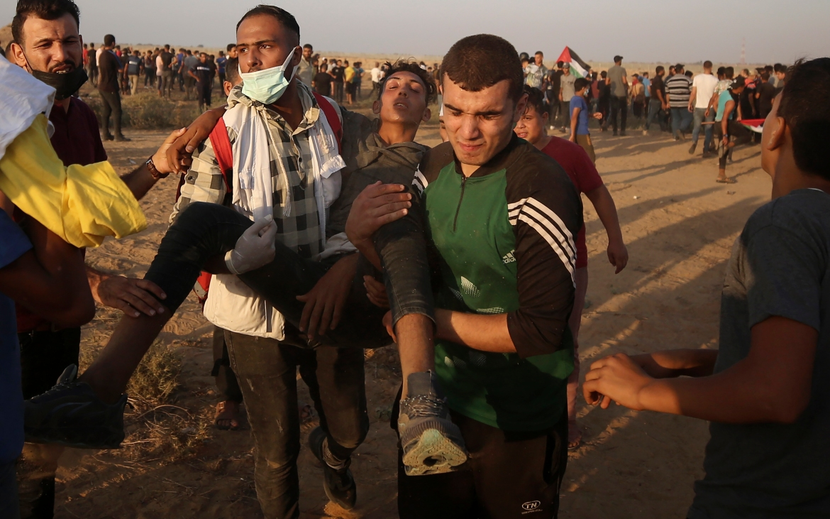 Protesters evacuate a wounded youth during the protest east of Khan Younis. [Abdel Kareem Hana/AP Photo]