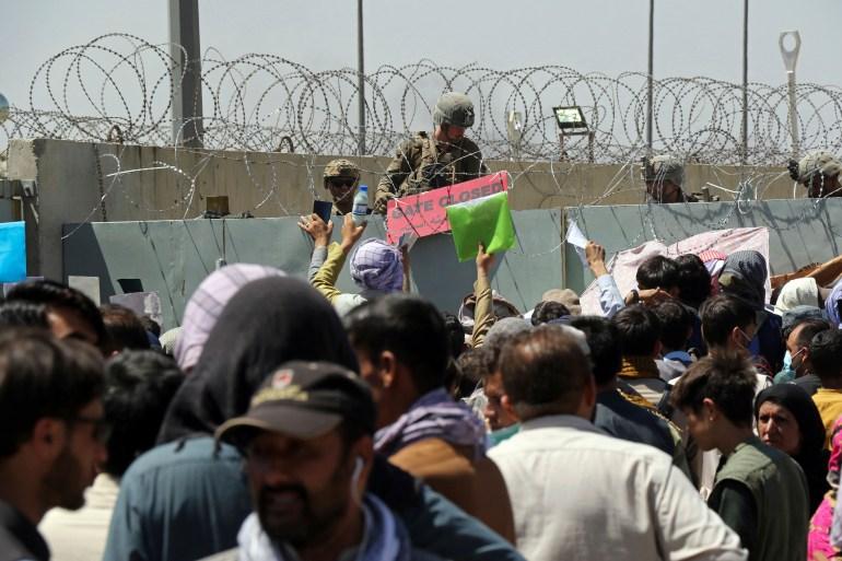 Um soldado dos EUA segura uma placa indicando que um portão está fechado enquanto centenas de pessoas se reúnem perto de um posto de controle de evacuação no perímetro do Aeroporto Internacional Hamid Karzai, em Cabul, Afeganistão, em 26 de agosto [File: Wali Sabawoon/AP Photo]