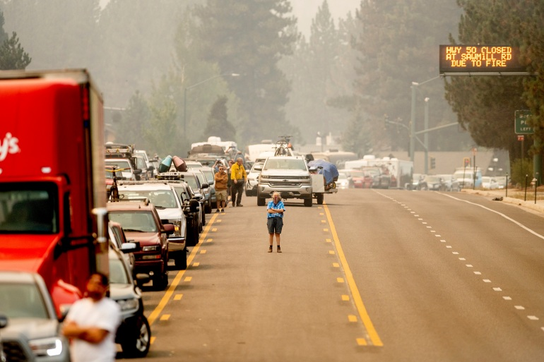 With the Caldor Fire approaching, Dawn Svymbersky stands in the middle of Highway 50 as evacuee traffic stands still in South Lake Tahoe, California [Noah Berger/AP Photo]