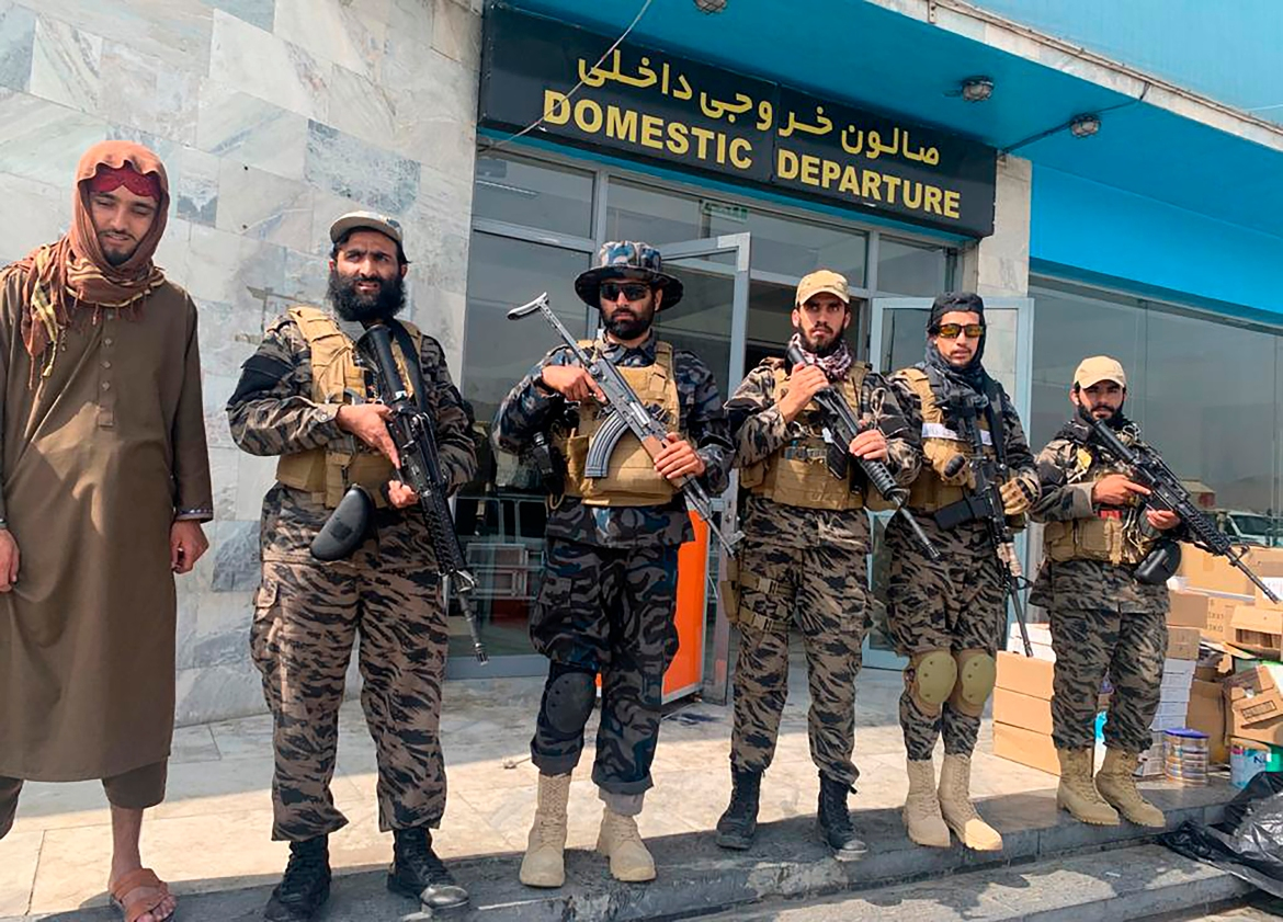 Taliban fighters stand guard inside the Hamid Karzai International Airport after the US withdrawal. [Kathy Gannon/AP Photo]