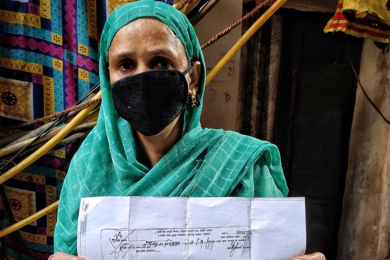 Tabassum Nisha segurando o recibo de 2013 de seu pedido de cartão de racionamento [Srishti Jaswal/Al Jazeera]
