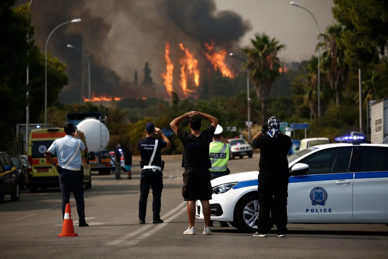 The blaze north of Athens has destroyed dozens of homes. [Yannis Kolesidis/EPA]