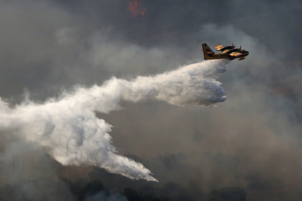 Seven water-dropping planes and nine helicopters were involved in the firefighting effort near Athens, including a Beriev Be-200 amphibious aircraft leased from Russia. [Orestis Panagiotou/EPA]