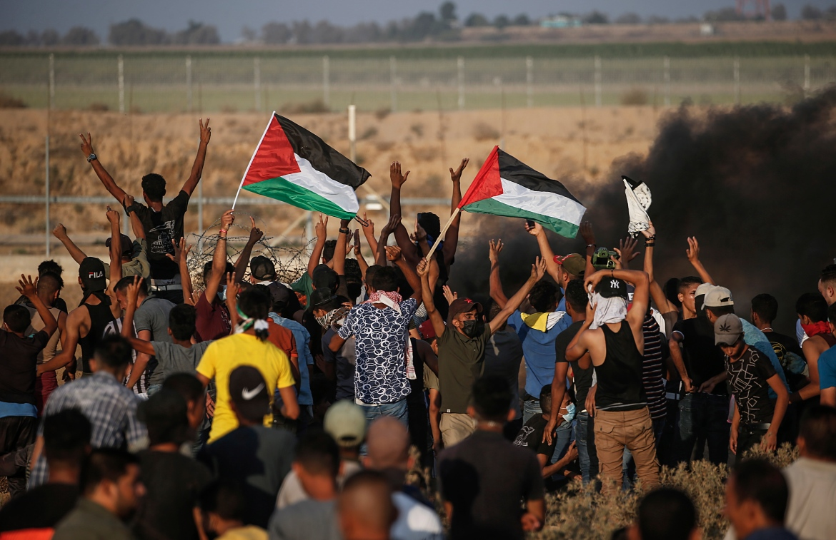 Palestinian protesters gather near the Israeli separation barrier between Israel and Gaza Strip. [Mohammed Saber/EPA]