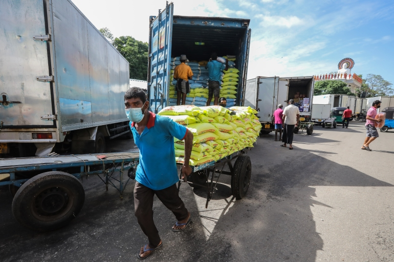 Workers unload essential food products at a wholesale market in Colombo, Sri Lanka [Chamila Karunarathne/EPA]