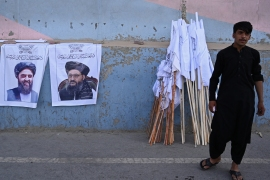 A vendor selling Taliban flags stands next to posters of Taliban leaders Mullah Abdul Ghani Baradar and Amir Khan Muttaqi (L) as he waits for customers along a street in Kabul on August 27, 2021. [Aamir Qureshi/ AFP]