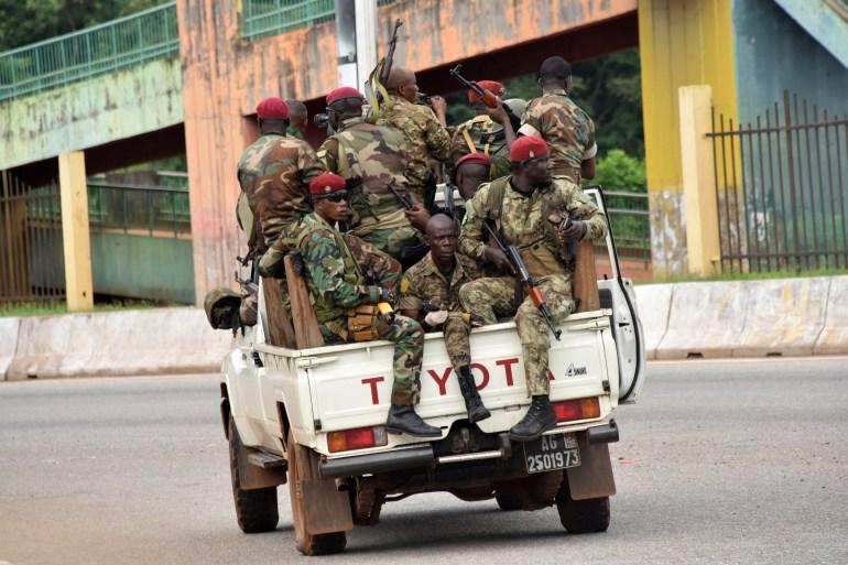 Membros das Forças Armadas da Guiné dirigem pelo bairro central de Kaloum, em Conakry, no domingo, após ouvir tiros sustentáveis [Cellou Binani/AFP]