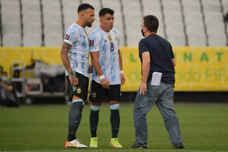 An employee of Brazil's National Health Surveillance Agency (Anvisa) argues with Argentina's Nicolas Otamendi (L) and Marcos Acuna during the South American qualification football match for the FIFA 2022 World Cup at Neo Quimica Arena in Sao Paulo, Brazil, on September 5 [Nelson Almeida/AFP]