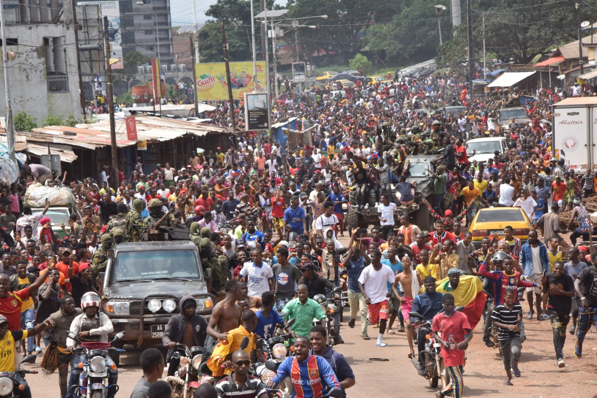 People celebrate on the streets with members of Guinea's armed forces after the arrest of President Alpha Conde. [Cellou Binani/AFP]
