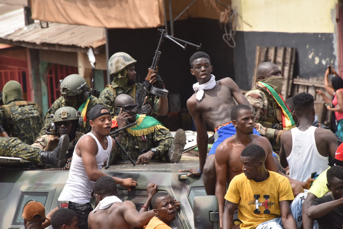 """People celebrate with members of Guinea's armed forces on Sunday. The Economic Community of West African States (ECOWAS) threatened to impose sanctions while the African Union said it would meet urgently and take """"appropriate measures"""". [Cellou Binani/AFP]"""