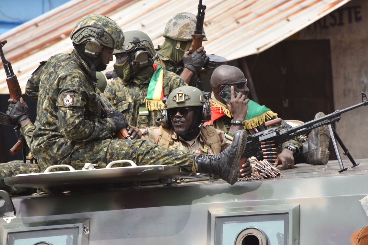 Members of Guinea's armed forces celebrate after the arrest of the president. [Cellou Binani/AFP]