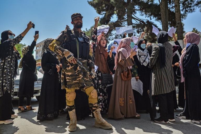 Um combatente do Taleban fica de guarda enquanto mulheres afegãs gritam slogans durante um protesto em Cabul [Hoshang Hashimi/AFP]