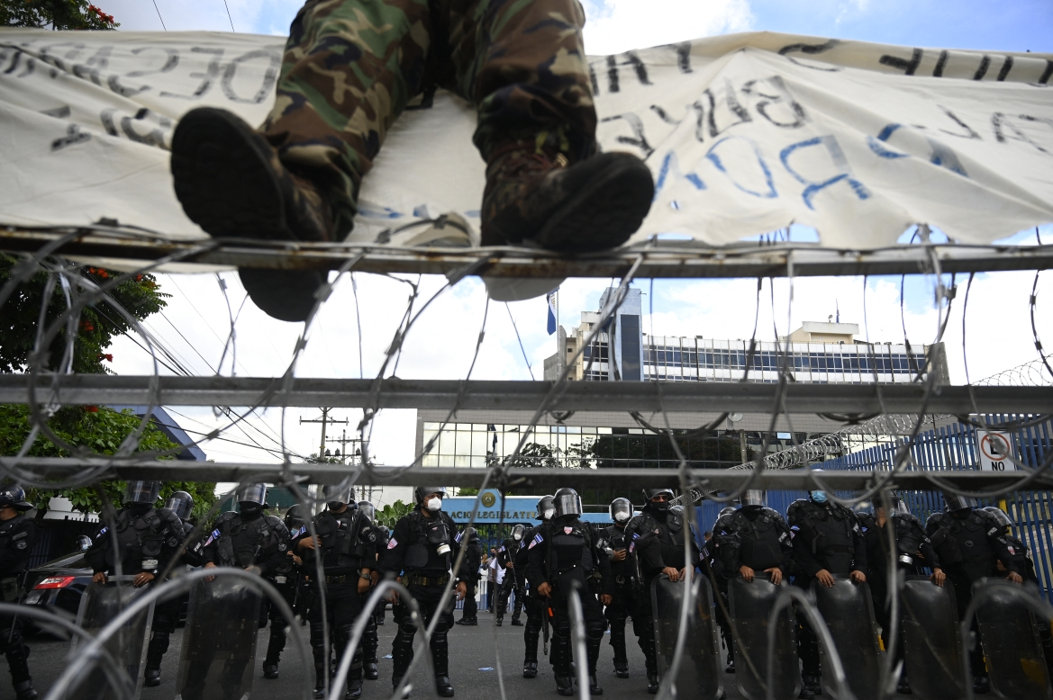Riot police stand guard during the protest against the circulation of Bitcoin in San Salvador. [Marvin Recinos/AFP]