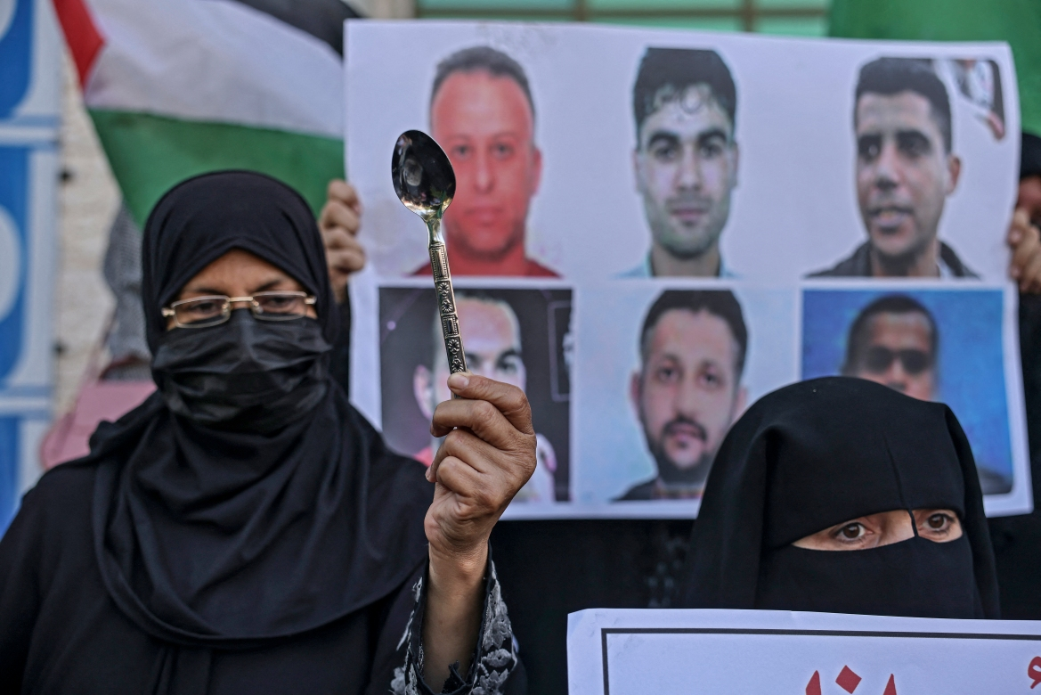 A demonstrator holds up a spoon during a rally in solidarity with the six Palestinian political prisoners in Khan Yunis. [Said Khatib/AFP]
