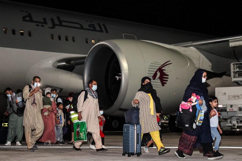 Passageiros do Afeganistão chegam ao Aeroporto Internacional de Hamad, na capital do Catar, Doha, no primeiro vôo que transporta estrangeiros da capital afegã desde a conclusão da retirada dos Estados Unidos [Karim Jaafar/AFP]