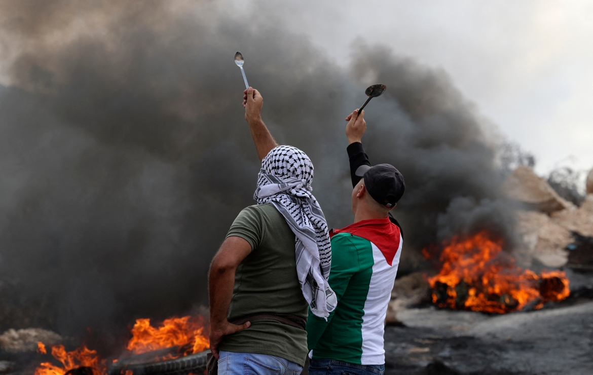 Palestinian protesters hold up spoons as they confront Israeli security forces following a demonstration in the West Bank village of Beita. [Jaafar Ashtiyeh/AFP]