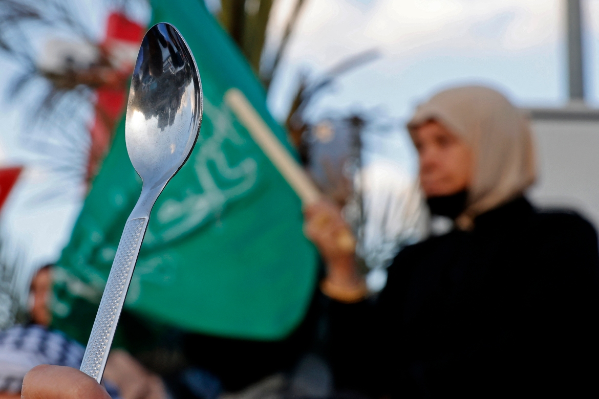 Palestinian citizens of Israel hold up spoons as they protest in the mostly Palestinian city of Umm al-Fahm in northern Israel. The six Palestinian prisoners escaped through a tunnel on September 6 from the high-security Gilboa prison. [Jack Gues/AFP]