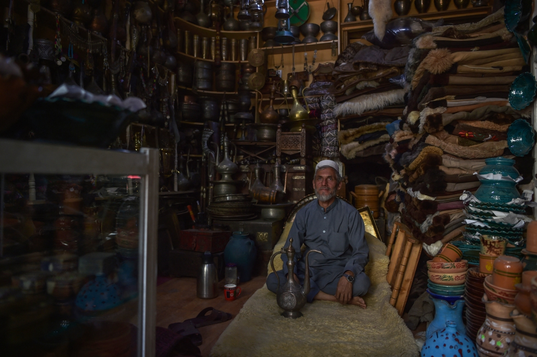 A pottery vendor sits inside his shop as he waits for customers. [Wakil Kohsar/AFP]