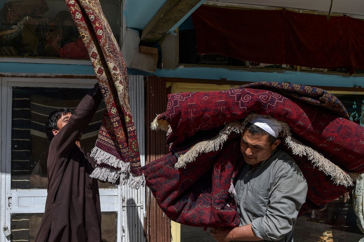 Workers carry carpets at Chicken Street. Tourism plummeted after the Soviet invasion of Afghanistan in 1979. [Wakil Kohsar/AFP]