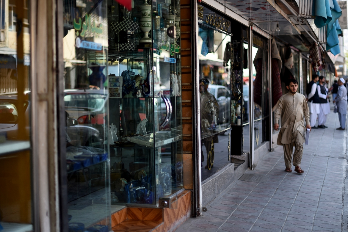 A man walks along rows of shops selling antiques and decorative merchandise on Chicken Street. [Wakil Kohsar/AFP]