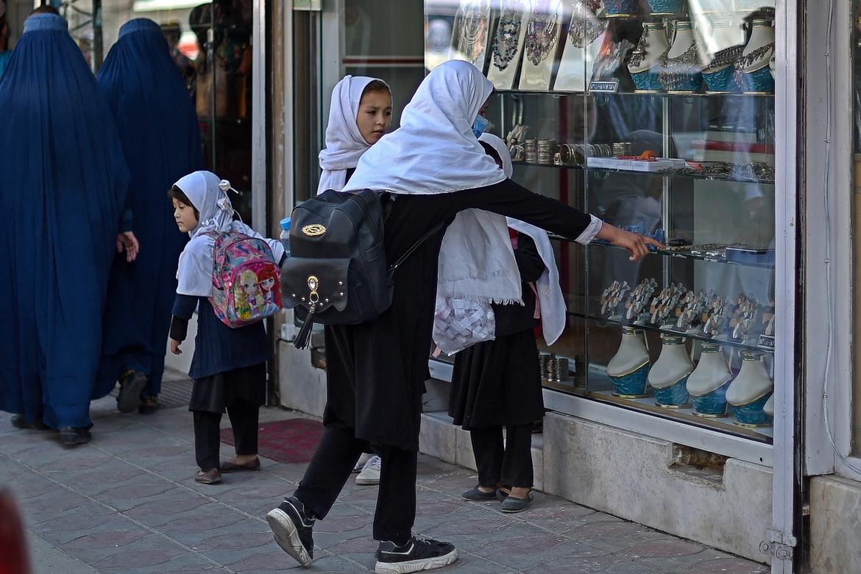 Afghan schoolgirls look at jewellery displayed on a window shelf of a shop on Chicken Street. [Wakil Kohsar/AFP]