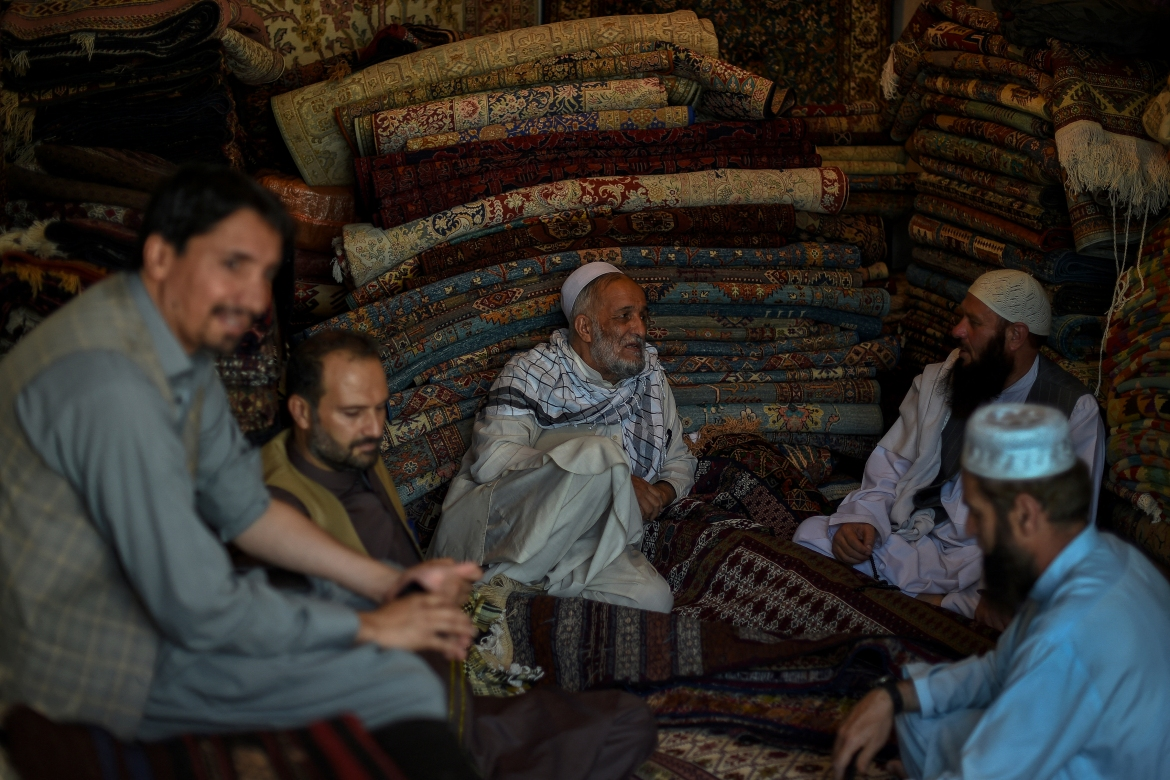 Afghan carpet vendors inside a carpet shop at Chicken Street. The once-bustling hotspot, where aid workers and adventurous tourists would shop for vintage tribal rugs, pottery and metalware, is almost empty of visitors looking for a bargain. [Wakil Kohsar/AFP]