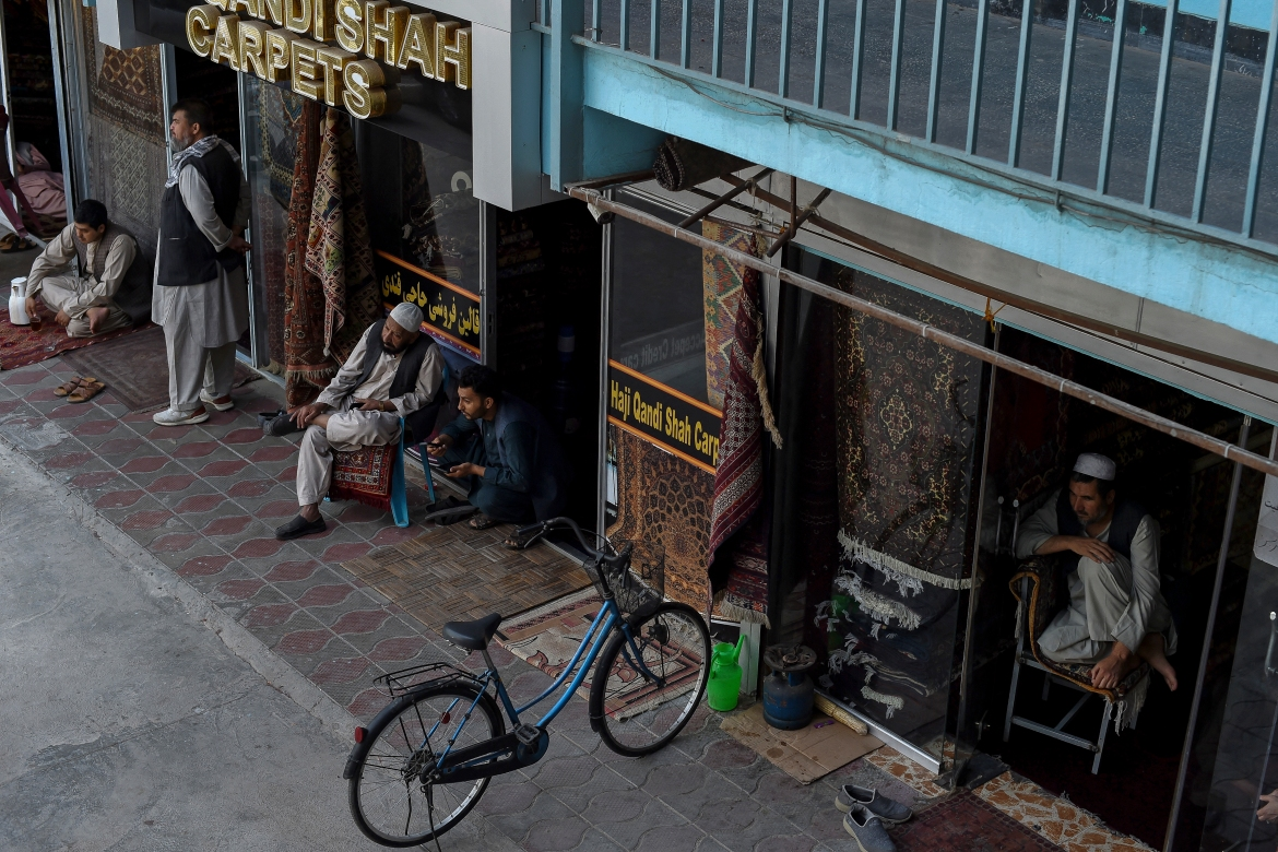 Afghan carpet vendors sit in front of their shops. [Wakil Kohsar/AFP]