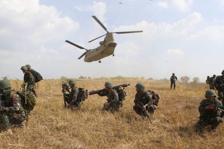Soldados filipinos tomam posição enquanto um helicóptero militar dos EUA decola durante jogos de guerra entre os militares dos dois países em um acampamento no norte das Filipinas [File: Erik De Castro/Reuters]