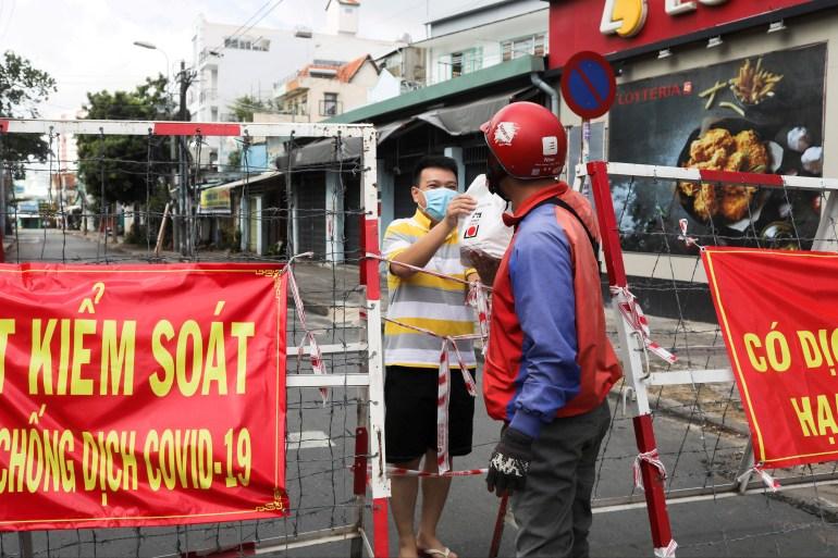 Um homem que vive em uma área confinada recebe comida por meio de uma barricada durante a pandemia COVID-19 na cidade de Ho Chi Minh, Vietnã, 20 de julho de 2021 [File: Reuters]