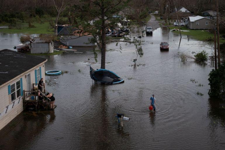 Um homem volta para sua casa depois de compartilhar combustível com seus vizinhos para usar em seus geradores após o furacão Ida em Cut Off, Louisiana, em 30 de agosto [File: Adrees Latif/Reuters]