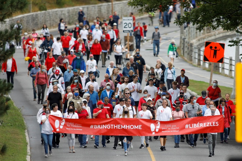 Supporters of Kovrig and Spavor march to mark 1,000 days since the Canadians were arrested in China, during a protest in Ottawa, Canada, September 5 [Blair Gable/ Reuters]