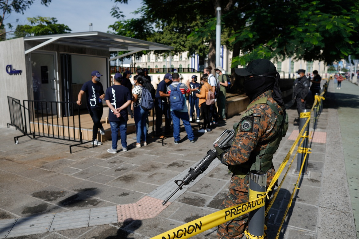 A soldier stands guard while people ask for information about the use of Bitcoin outside an ATM of Chivo wallet, a Bitcoin wallet the Salvadoran government is launching for the use of Bitcoin as a legal tender, in San Salvador. [Jose Cabezas/Reuters]