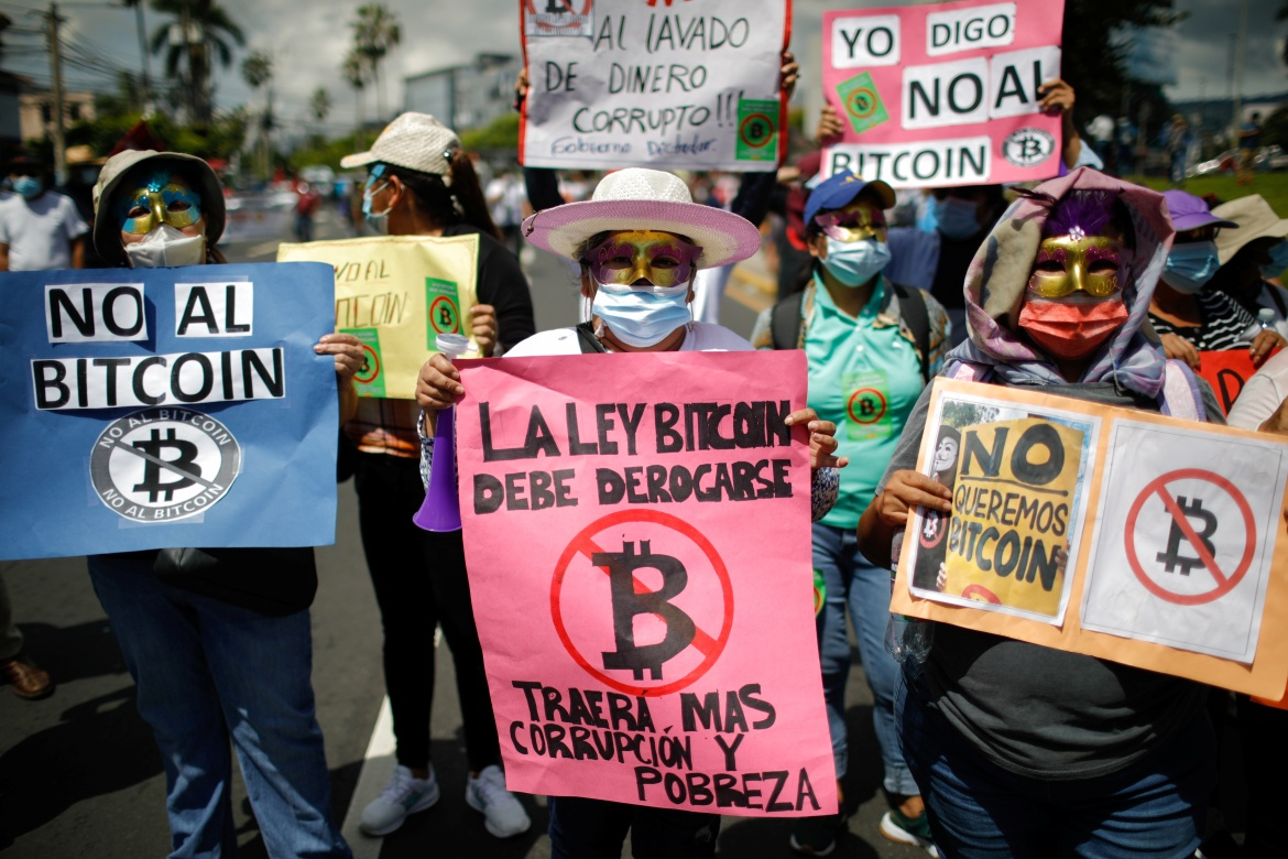 A person holds a sign that reads 'The Bitcoin bill must be repealed, it will bring more corruption and poverty', as people protest against its use in San Salvador. [Jose Cabezas/Reuters]