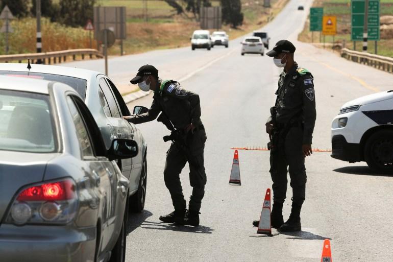 Forças de segurança israelenses param um carro em um bloqueio de estrada como parte dos esforços de busca para capturar os homens palestinos [Ammar Awad/Reuters]